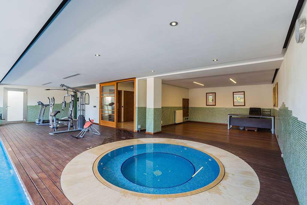 Wellnessbereich mit Innenpool, Whirlpool und einige Fitnessgeräte.