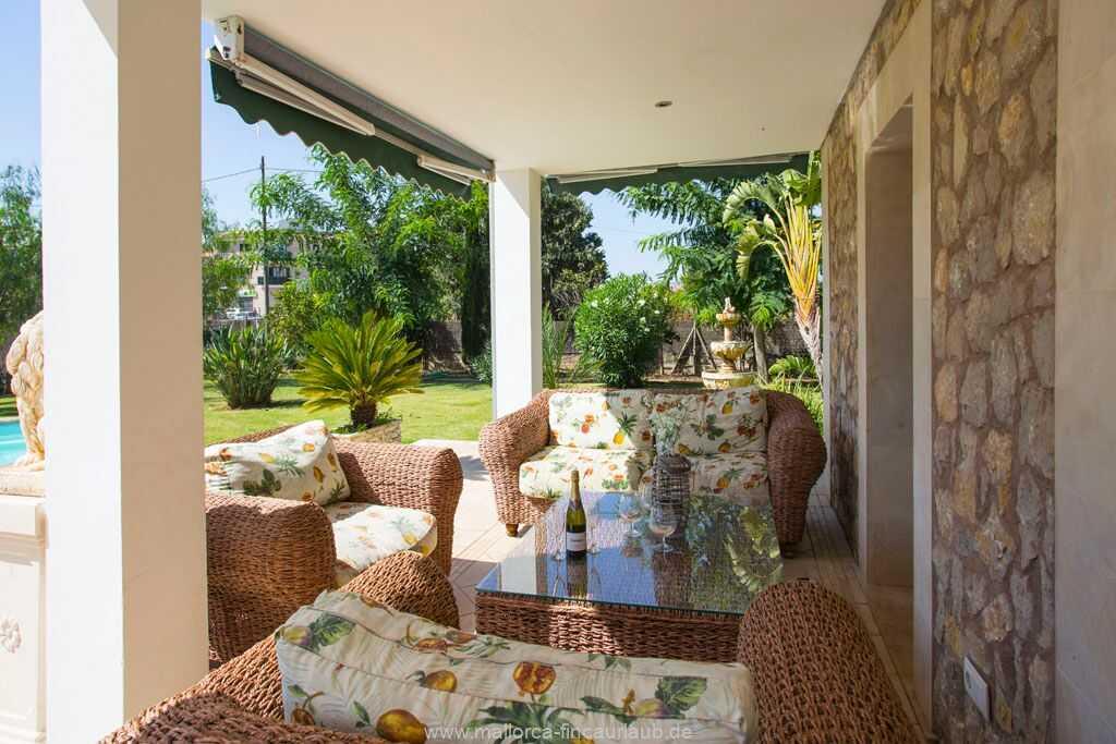 überdachte Terrasse mit Esstisch für 6 Personen und Blick zum Pool